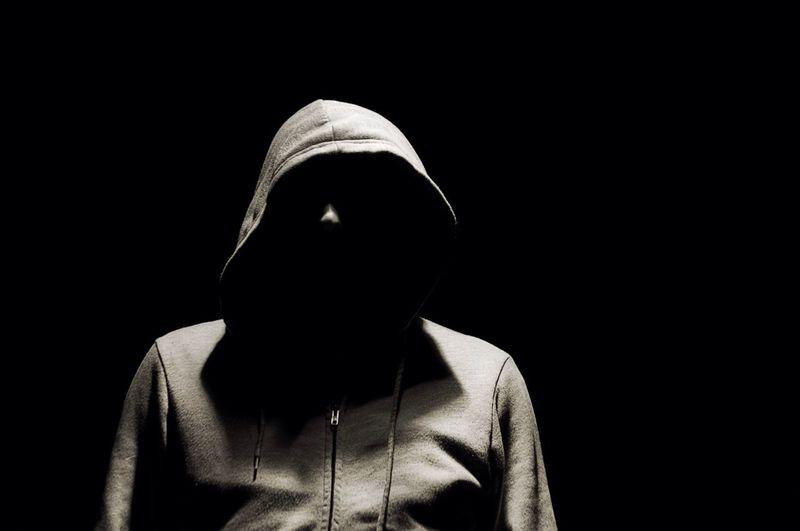 Man in hooded jacket over black background