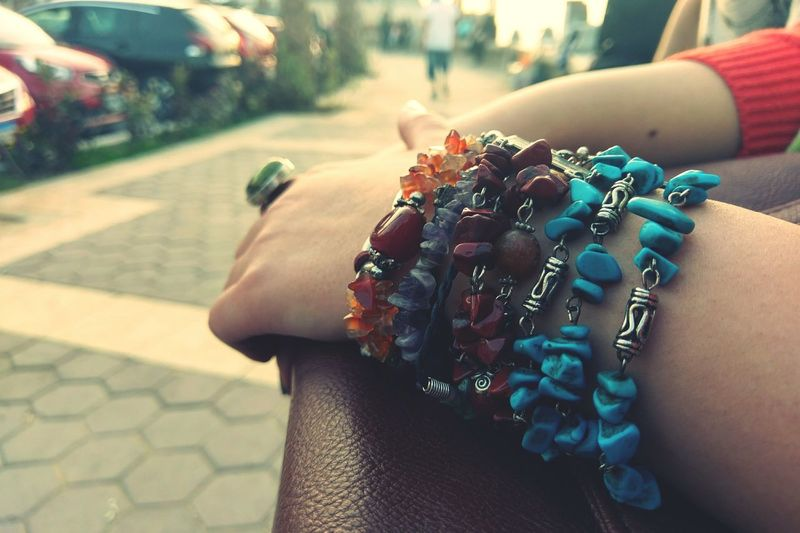 Cropped hands of woman wearing bracelet outdoors
