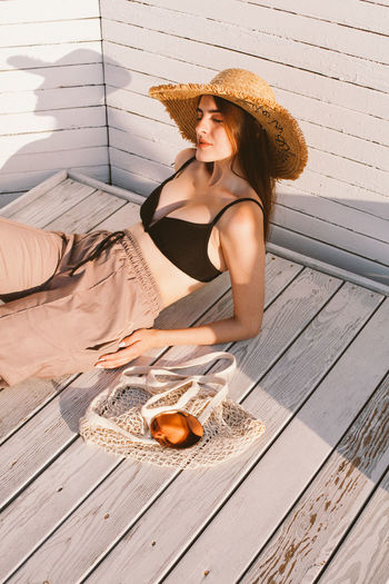 Full length of woman sitting on table outdoors