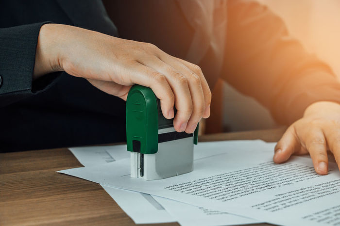 Close-up hand stamping of business woman for signing approval on documents Business Check Desk Lawyer Office Officer Papaer Woman Worker Working Agree Agreement Approve Contract Document Documentation Finance Sheet Signature Signing Space Stamp Stamping