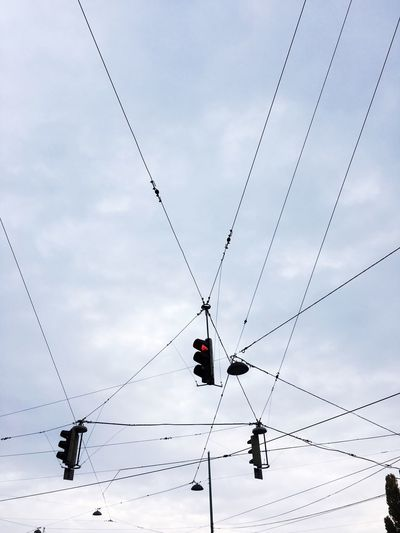 Low Angle View Of Stoplights Hanging Against Cloudy Sky