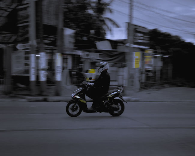 Man riding motorcycle on street in city