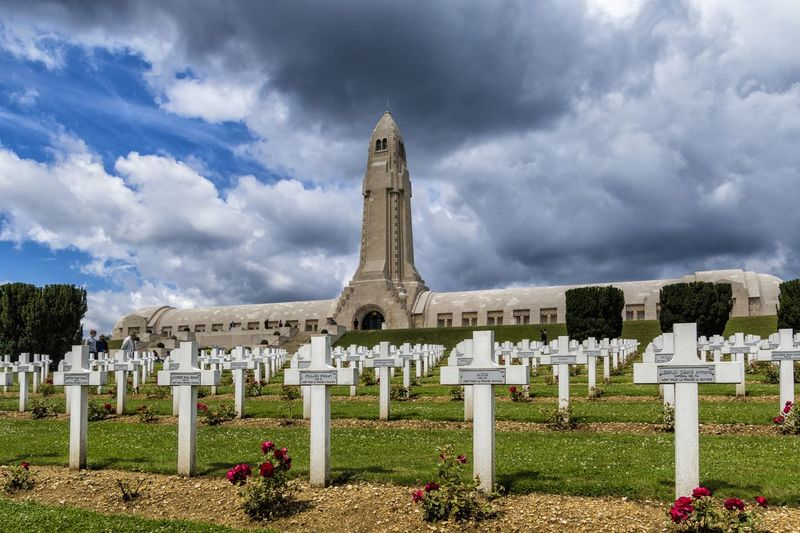 """The Douaumont ossuary (French: L'ossuaire de Douaumont) is a memorial containing the skeletal remains of soldiers who died on the battlefield during the Battle of Verdun in World War I. It is located in Douaumont, France, within the Verdun battlefield. It was built on the initiative of Charles Ginisty, Bishop of Verdun. It has been designated a """"nécropole nationale"""", or """"national cemetery"""" Battle Of Verdun Douaumont Ossuary L'ossuaire De Douaumont Ossuary Cemetery Cloud - Sky Cross Day Grave Gravestone Graveyard History History Place Memorial Monument Necropolis No People Outdoors Religion Sky Spirituality Tombstone Travel Destinations World War 1 World War 1 Memorial"""