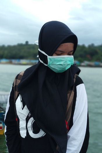 Woman wearing pollution mask by lake