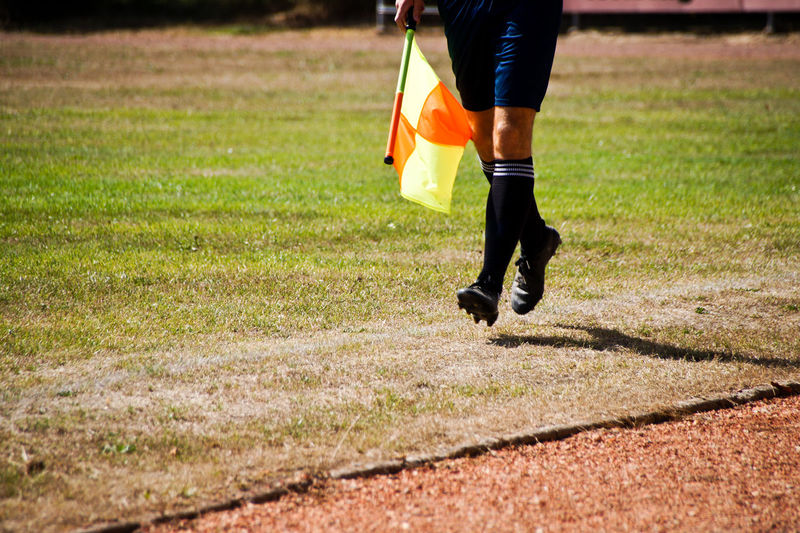 Low Section Of Soccer Player With Flag Running On Field