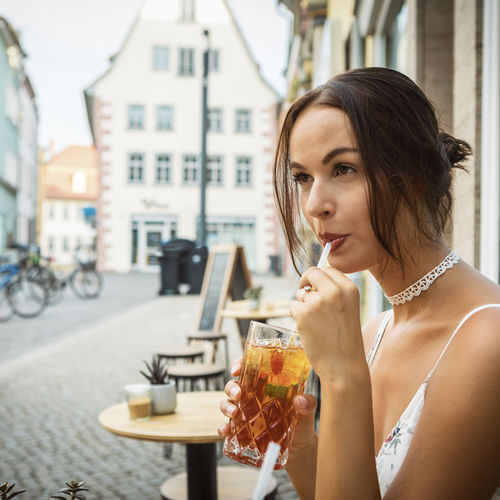young woman having ice tea Dress Happiness Reflection Summer Exploratorium Beautiful Woman Brunette Girl  Cafe Caucasian City Drink Enjoying Life Food And Drink Ice Tea Indoors  Lifestyles One Person Outdoors Refreshment Straw Table Window Women Young Adult Young Adults Young Women