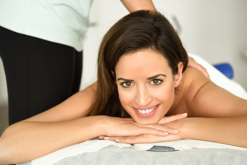 Young female receiving a relaxing back massage in a spa center. Brunette woman patient is receiving treatment by professional therapist. Beautiful Woman Beauty Spa Close-up Day Happiness Health Care Health Care And Medical Human Hand Indoors  Leisure Activity Lifestyles Looking At Camera Lying Down Lying On Front Massage People Portrait Real People Relaxation Smiling Spa Young Adult Young Women