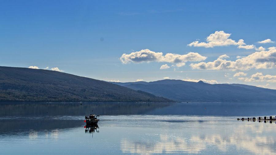 Scenic view of boat in loch fyne against sky