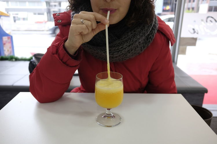 |midsection of woman having drink at restaurant