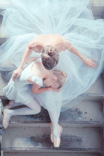 Directly above shot of ballet dancers sitting on staircase