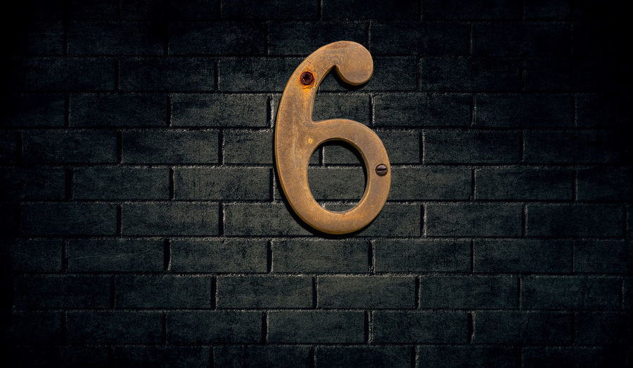 Number 6 on brick wall at night