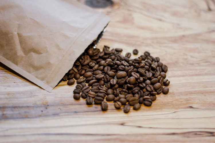 Food And Drink Food Roasted Coffee Bean Freshness Brown Coffee Table Coffee - Drink Wood - Material Still Life Close-up No People Indoors  Large Group Of Objects High Angle View Roasted Caffeine Spilling Raw Food Selective Focus Wood Grain