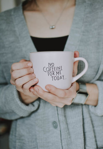 Midsection One Person Communication Text Holding Front View Real People Women Casual Clothing Cup Lifestyles Adult Indoors  Western Script Mug Human Hand Drink Refreshment Hand Message