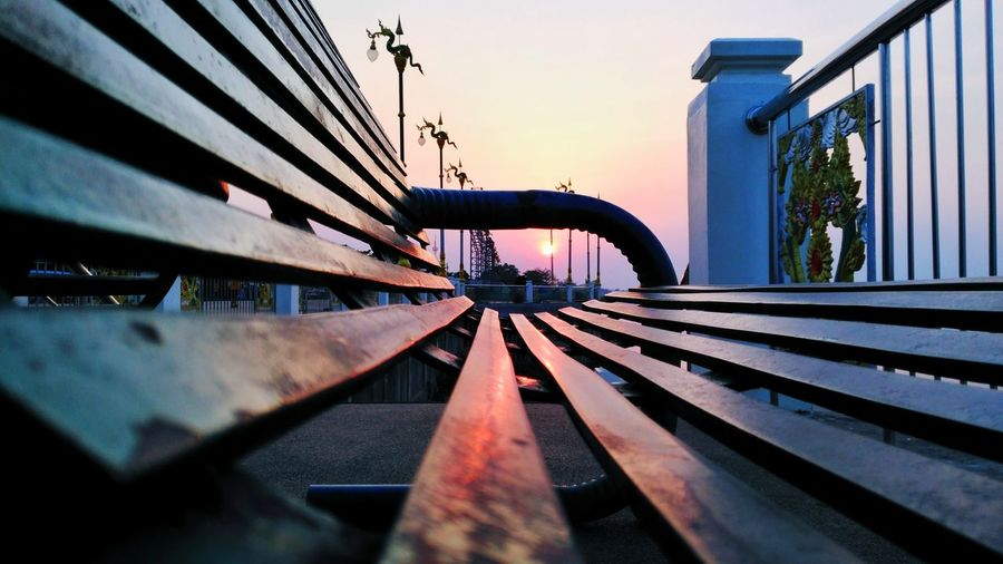 Close-up of empty bench against sky during sunset