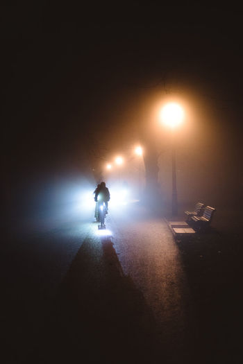 City Dark Direction Full Length Illuminated Lighting Equipment Men Mode Of Transportation Night One Person Real People Rear View Riding Road Street Street Light The Way Forward Transportation Unrecognizable Person Walking