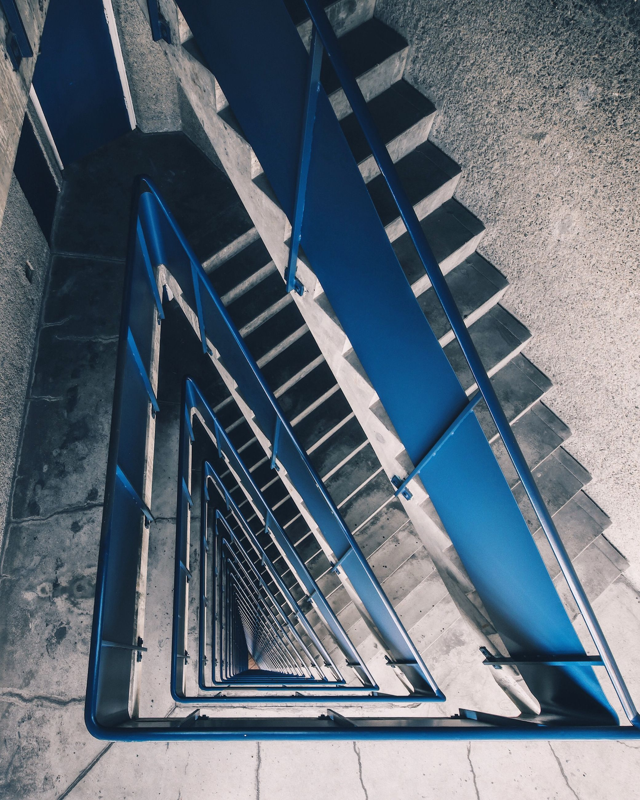 architecture, built structure, high angle view, staircase, no people, steps and staircases, day, building exterior, blue, railing, metal, building, pattern, outdoors, nature, spiral, directly above, sunlight, wall - building feature