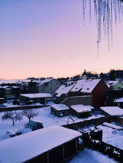 High angle view of snow covered houses against sky during sunset