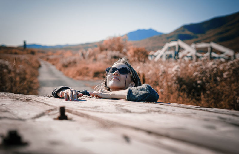 Woman lying down on wood against sky