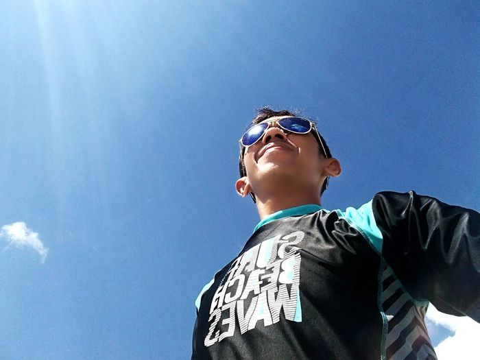 Low angle view of boy wearing sunglasses against clear blue sky