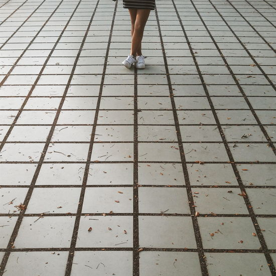 Low Section Of Woman With Legs Crossed At Ankle While Standing On Walkway