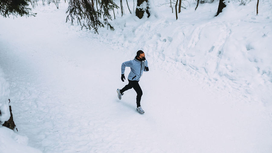 Man running on snow covered field