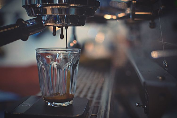 Close-up of coffee pouring into drinking glass at cafe