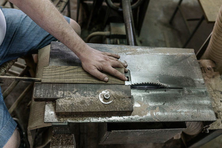 Midsection of man working on metal machine