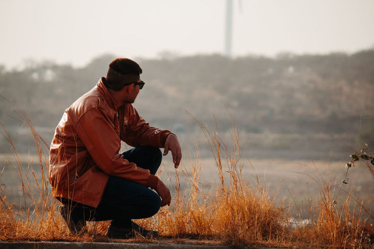 Man crouching against mountains
