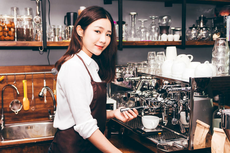 Women Barista using coffee machine for making coffee in the cafe Bar - Drink Establishment Bar Counter Barista Business Cafe Coffee Maker Coffee Shop Drink Food And Drink Hair Hairstyle Indoors  Looking At Camera Occupation One Person Portrait Preparation  Real People Refreshment Restaurant Smiling Standing Waist Up Women Young Adult