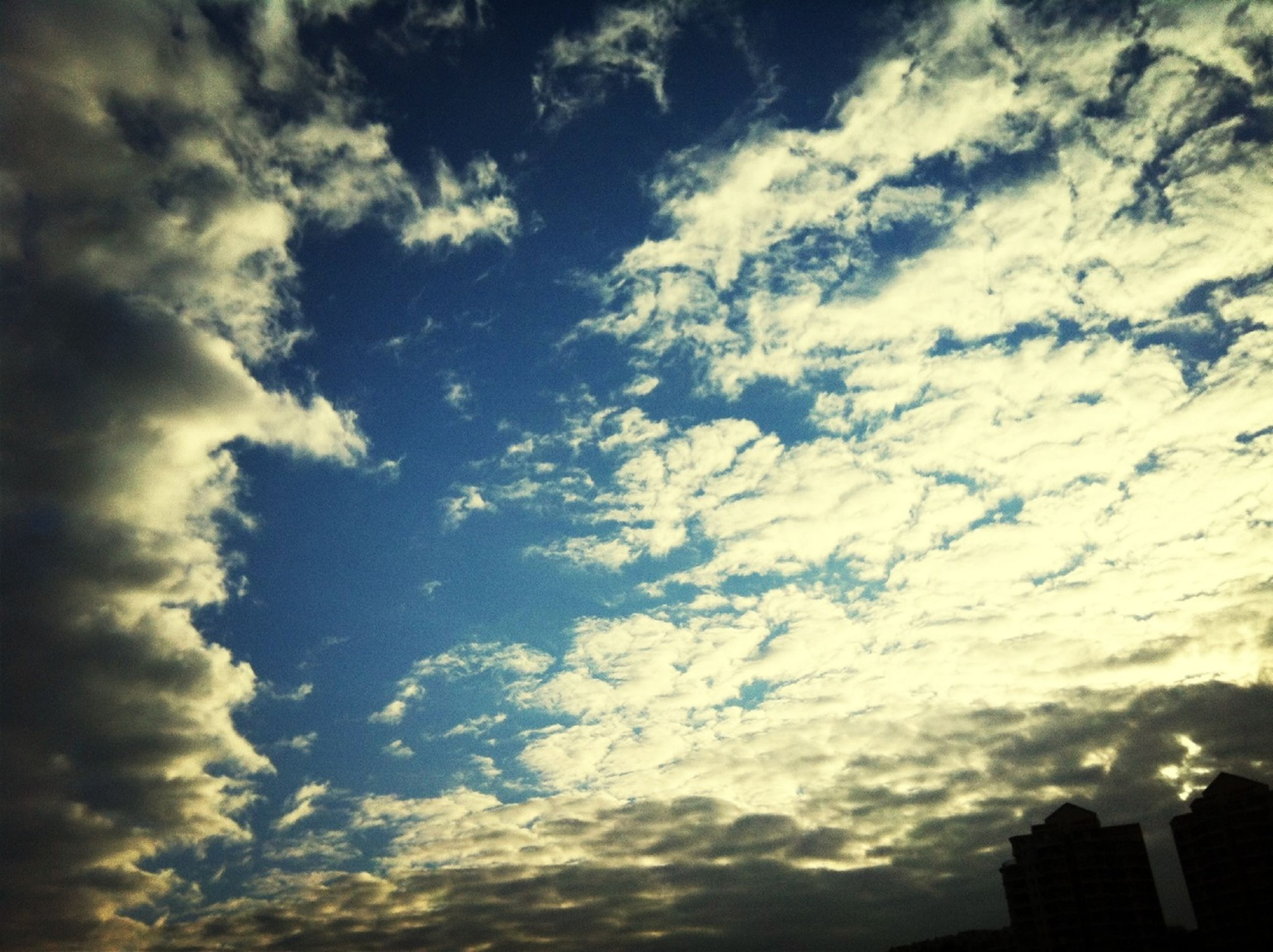 low angle view, sky, cloud - sky, cloudy, cloud, building exterior, beauty in nature, nature, silhouette, built structure, architecture, cloudscape, scenics, high section, weather, outdoors, tranquility, no people, sunset, overcast