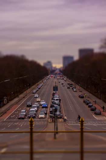 Tilt-shift image of cars on two lane highway at sunset