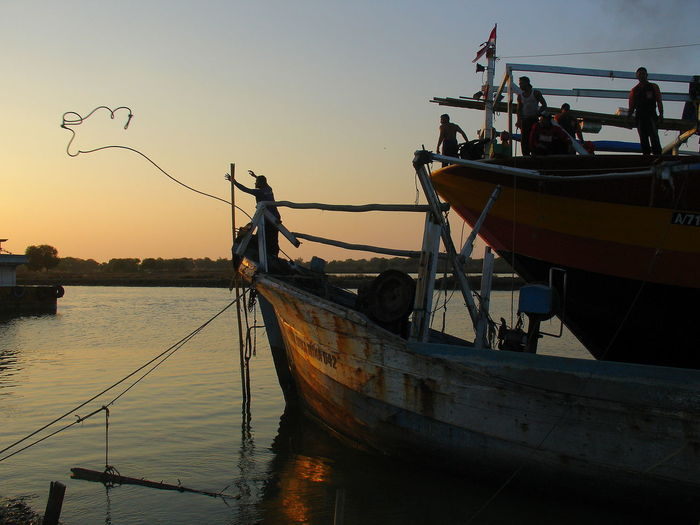 Fishing boat moored in sea against clear sky during sunset