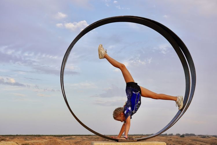 View of girl in gymnastic move in a circle