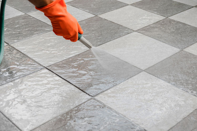 Hand of man wearing orange rubber gloves is use a hose to clean the tile floor. Body Part Day Flooring High Angle View Human Body Part Human Leg Human Limb Lifestyles Limb Low Section Men Motion One Person Outdoors Real People Tile Tiled Floor Unrecognizable Person Walking Working