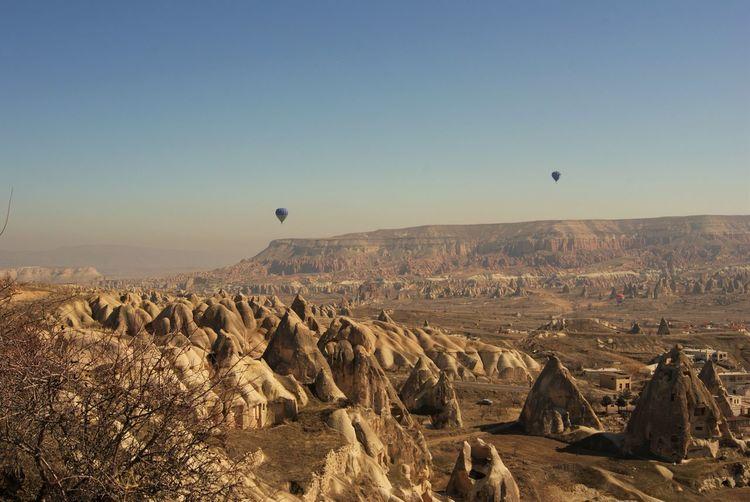 Hot air balloons flying over landscape at cappadocia