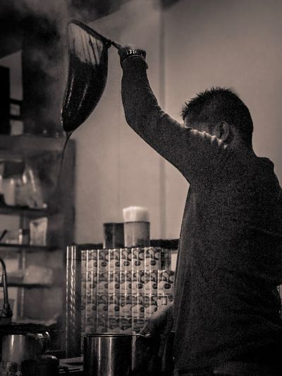 Side view of man cooking food in kitchen