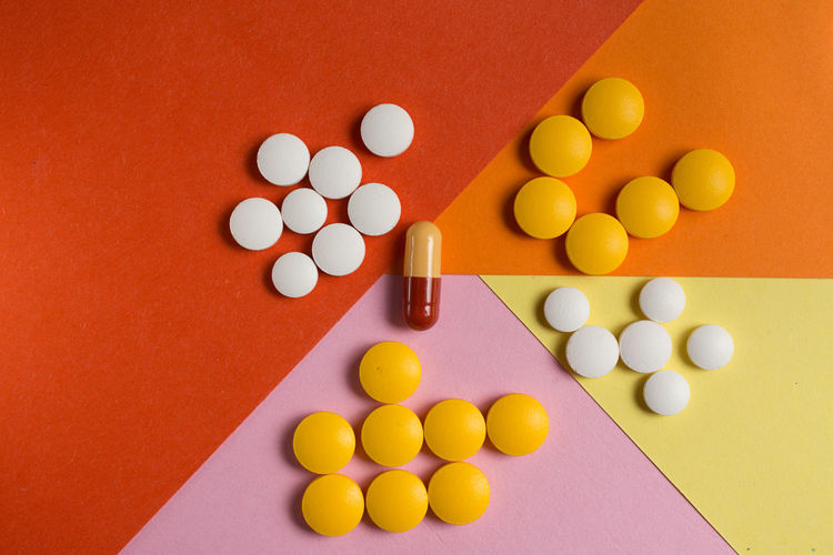 Pill Healthcare And Medicine Dose Large Group Of Objects Medicine Indoors  Nutritional Supplement No People Multi Colored Capsule Variation Studio Shot Orange Color High Angle View Choice Close-up Still Life Yellow Colored Background Table Vitamin C