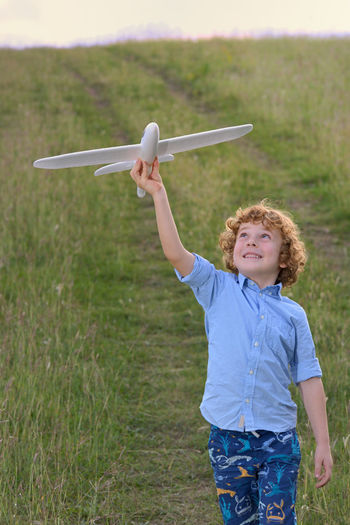 Boy playing with toy airplane on grassy field
