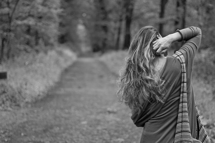 Rear view of woman with long hair standing on footpath