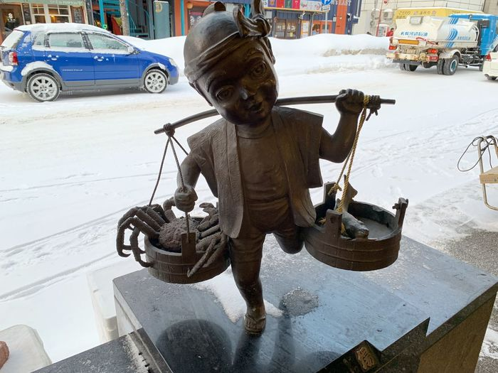 Statue on street in city during winter