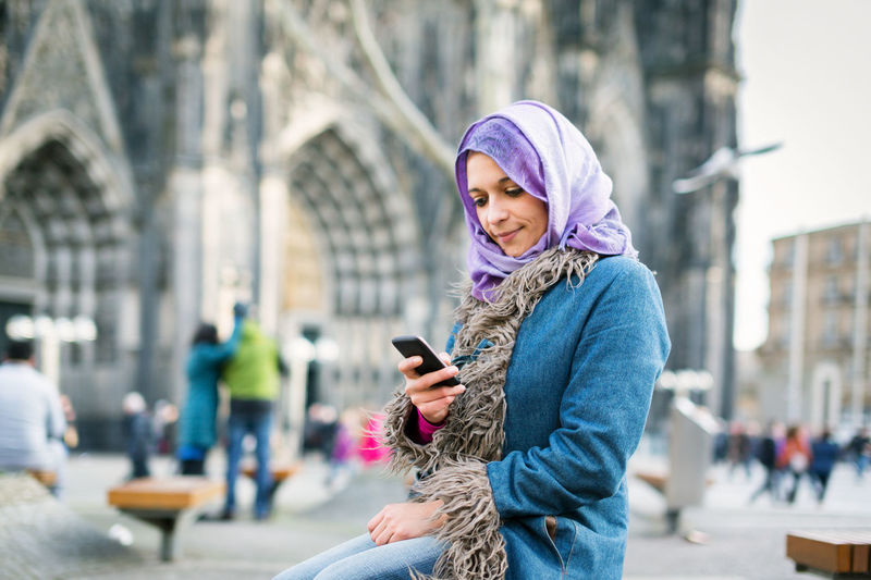 Cathedral Church City City Life Lifestyle Urban Scene Winter City City Life Headscarf Lifestyles Mobile Phone Muslim One Person Outdoors Real People Smart Phone Smiling Street Text Messaging Urban Setting Warm Clothing Wireless Technology Women Young Women Fresh On Market 2017