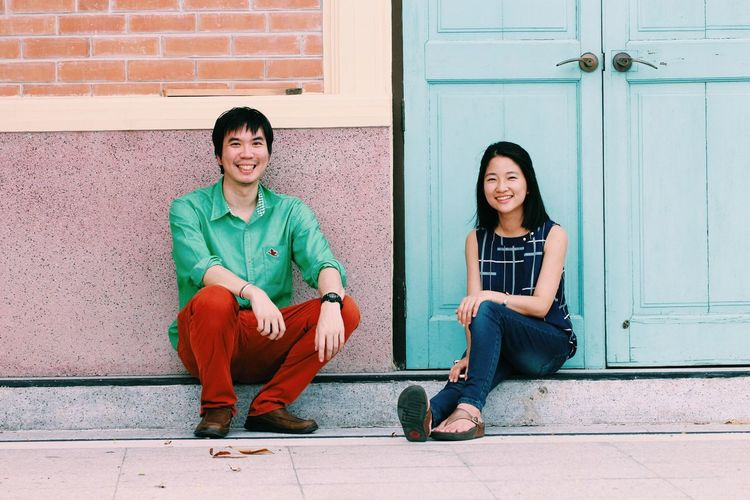 Asian man and women sitting on the floor Shirt Green Boy Woman Man Asian  Red Blue Wall Brick Door Wooden Family Love Couple EyeEm Selects Full Length Teenage Girls Happiness Outdoors Cheerful Portrait Day Architecture Building Exterior