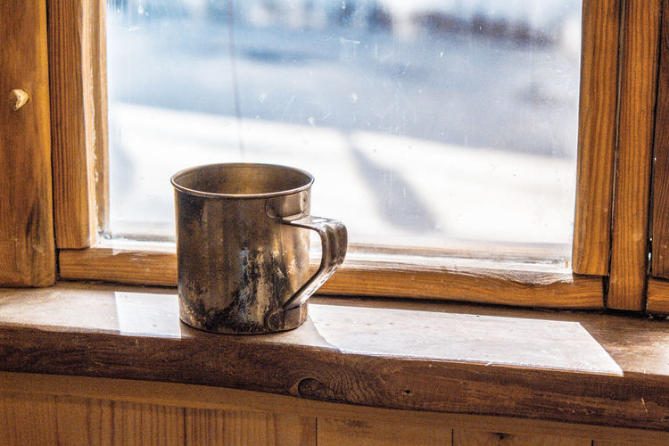 Old metal mug stands on a wooden window sill