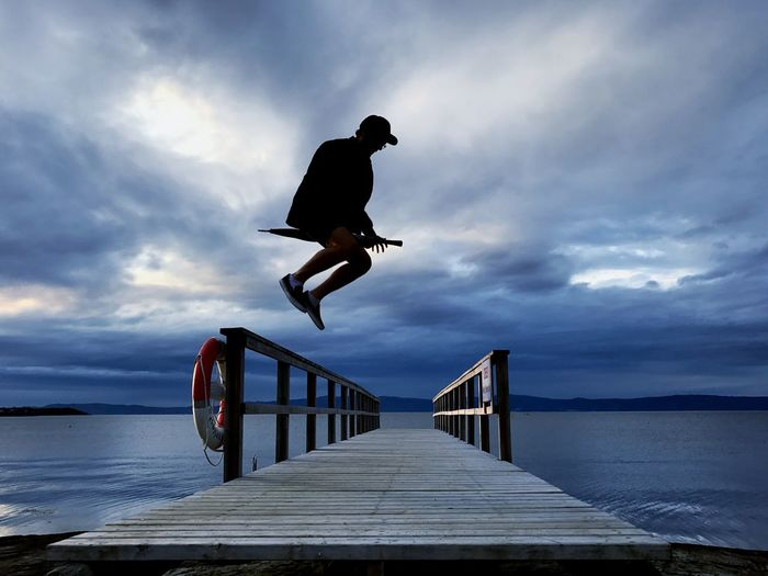 Man jumping over jetty against cloudy sky