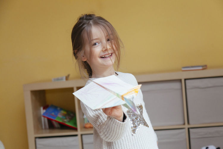 Portrait of smiling girl playing with paper airplane