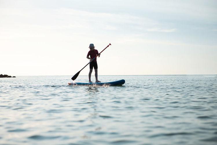 Full length of girl paddleboarding on sea against sky