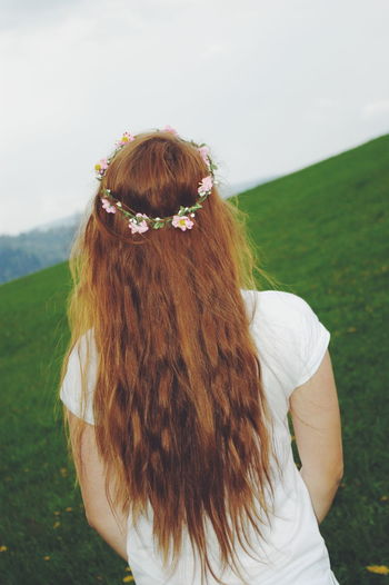 Rear view of redhead teenage girl standing outdoors
