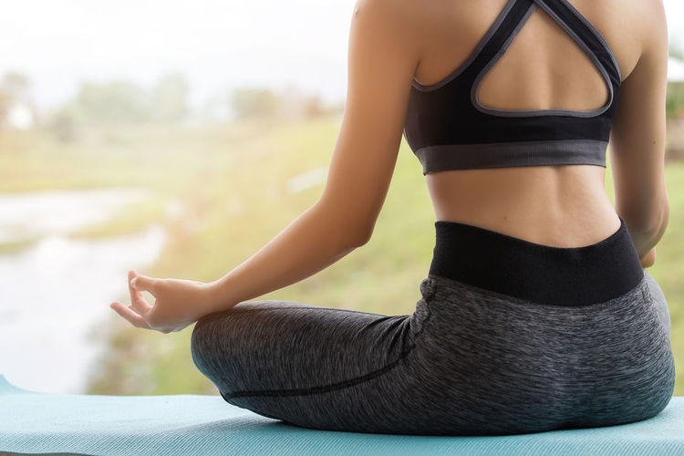 Midsection Of Young Woman Meditating While Sitting On Exercise Mat At Park