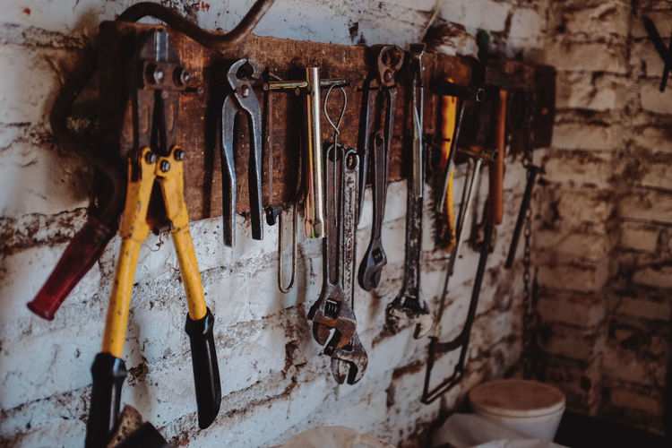 Close-up of various work tools hanging on wall in workshop