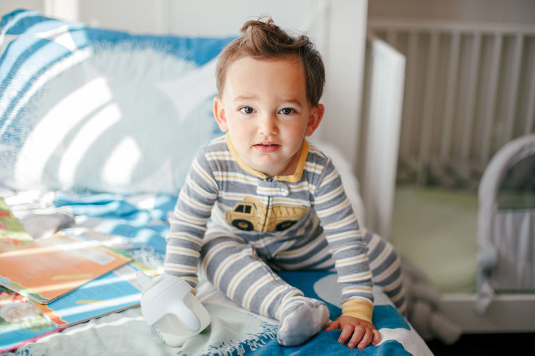 Cute adorable caucasian kid boy sitting on a bed drinking milk from kids bottle. healthy eating